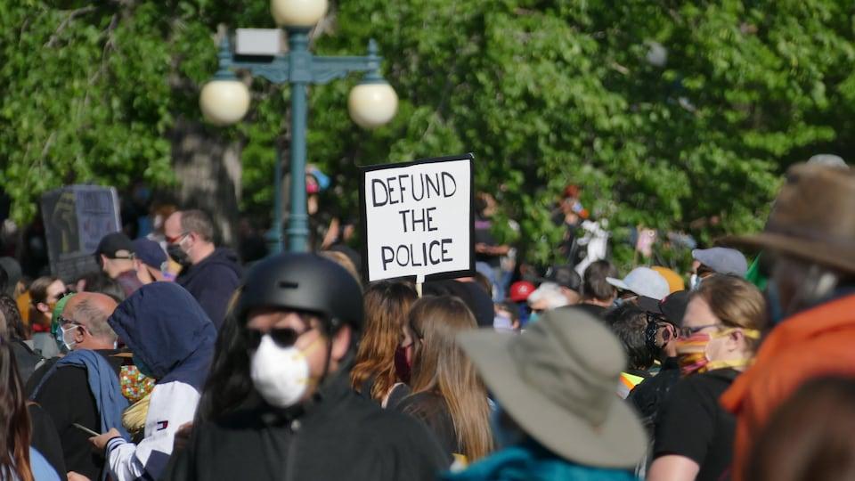 Une personne au centre d'une foule brandit une affiche où il est écrit en anglais : « Cessez de financer la police ».
