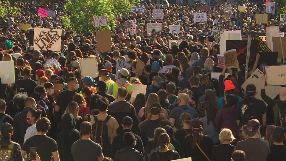 Plan large d'une foule dense qui remplit tout l'espace disponible, la majorité des participants brandissent une affiche.