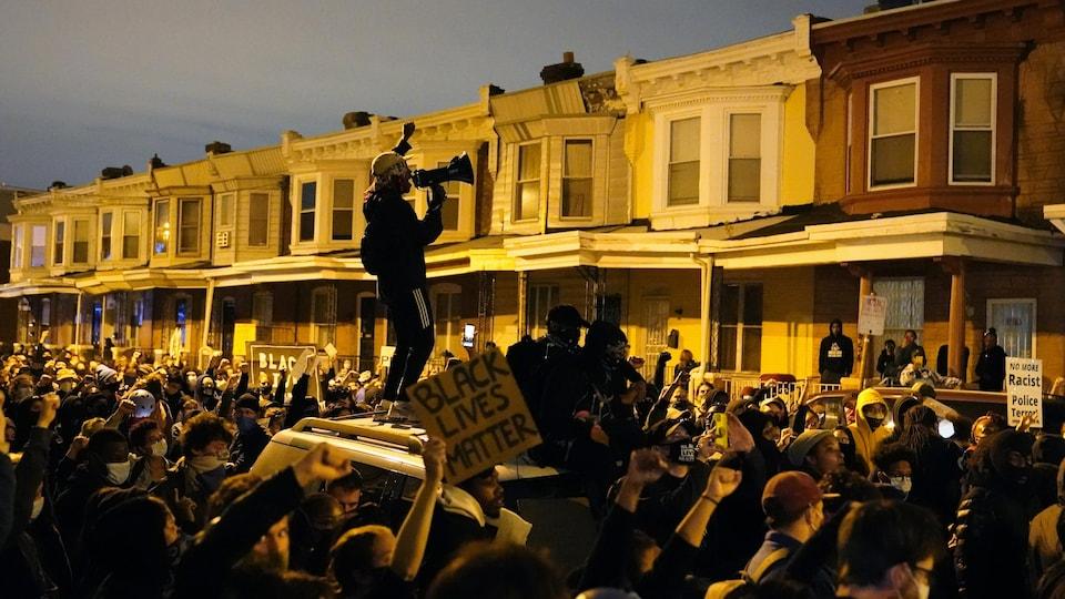 Un homme debout sur une voiture, au milieu de la foule, crie dans un porte-voix.