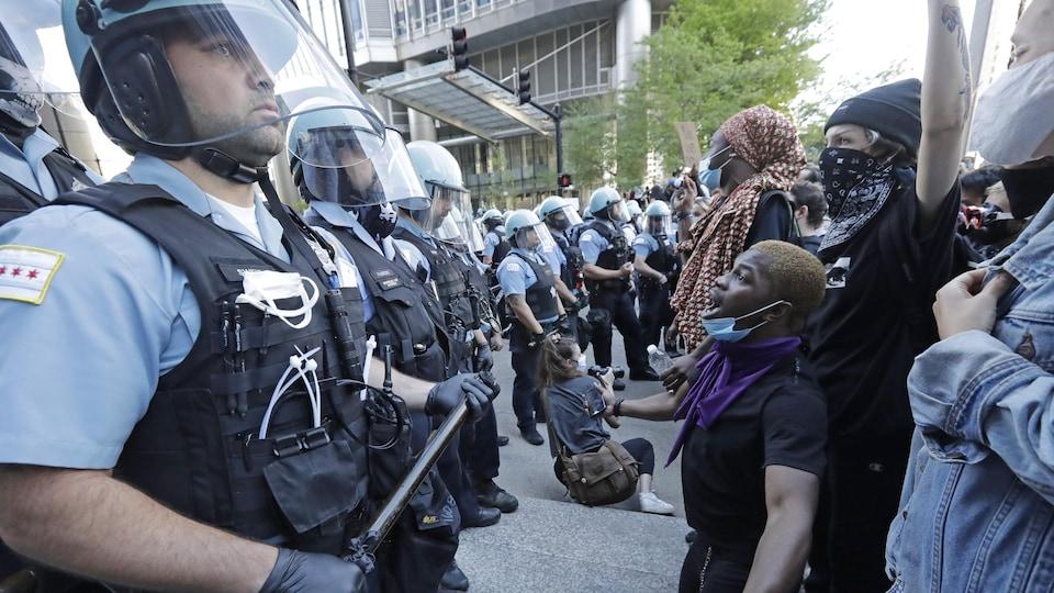 Une foule de manifestants se tient devant des policiers en rang.