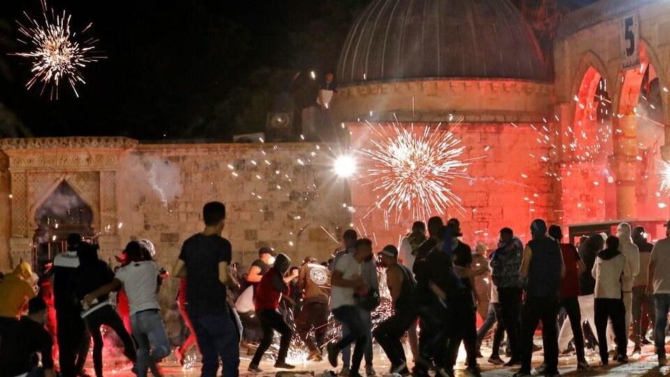 Un groupe de manifestants se tiennent devant la mosquée. Au-dessus de leurs têtes éclatent des grenades.