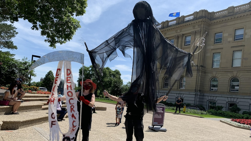 Une personne tient une grande marionnette de faucheuse, alors qu'une autre tient la faux avec des banderoles qui disent « mort de la démocratie » en anglais. Ils sont devant l'Assemblée législative.