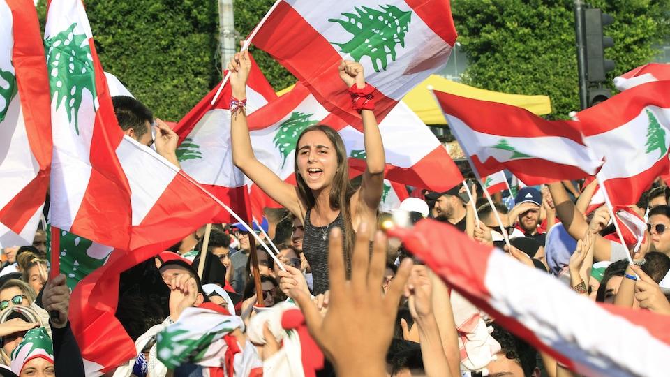 Une Libanaise au milieu d'une foule brandit un drapeau libanais à Sidon, le 19 octobre 2019.
