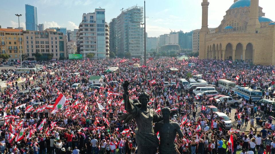 Une foule brandissant des drapeaux libanais.