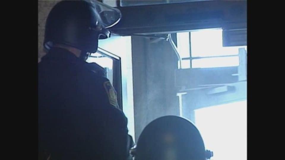 Deux agents de police portant des casques de protection devant la porte principale du palais législatif du Manitoba.
