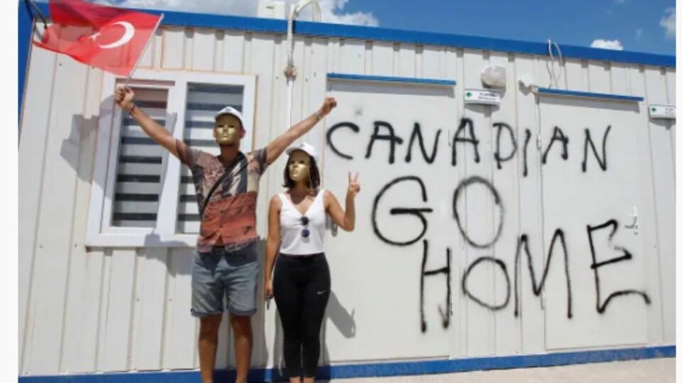 """Deux manifestants turcs arborent le drapeau de leur pays devant un édifice sur lequel il est écrit """"Canadiens, rentrez chez vous"""""""