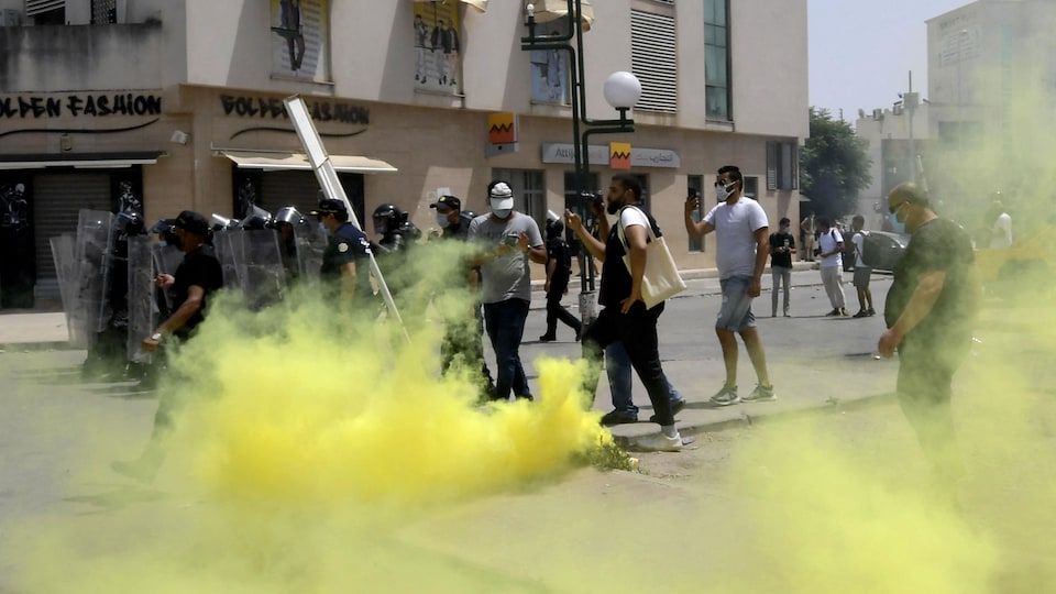 Les forces de sécurité tunisiennes derrière une fumée jaune déclenchée par des manifestants.