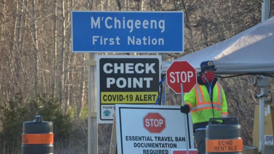 Un homme tient un panneau de signalisation sur lequel est inscrit « stop » à un point de surveillance.