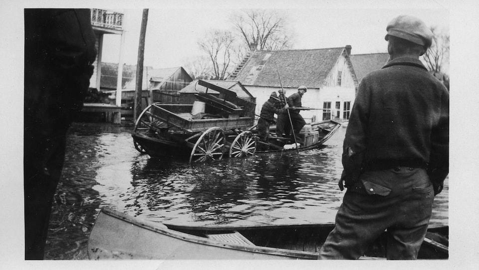 Une photo en noir et blanc montre un homme de dos et une charrette embarquée sur une barque que des citoyens tentent de faire avancer sur une rue inondée.