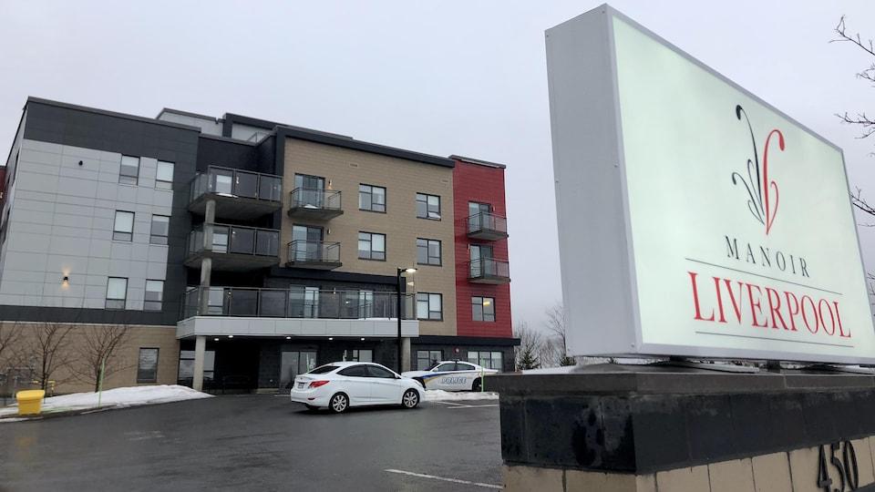 Affiche de couleur blanche devant un immeuble.