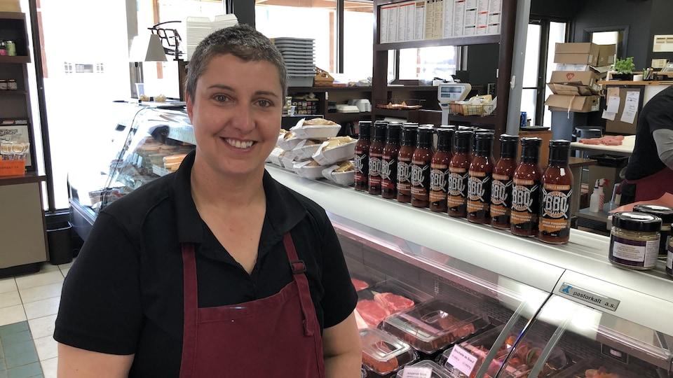 Manon Chamberland sourit devant le comptoir de sa boucherie.