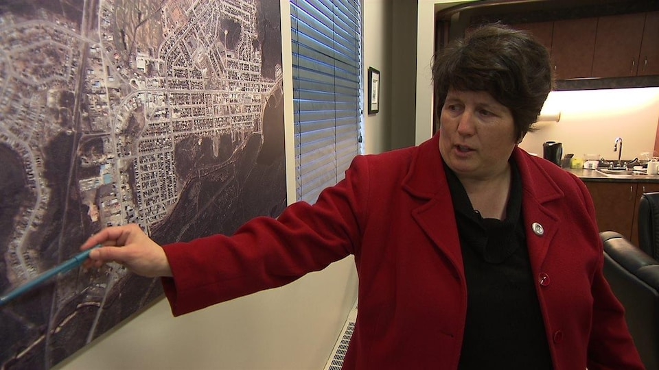 La mairesse de Chibougamau, Manon Cyr, pointe un schéma accroché au mur avec un crayon.