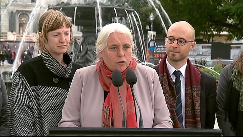 Manon Massé est en point de presse avec des candidats devant une fontaine.
