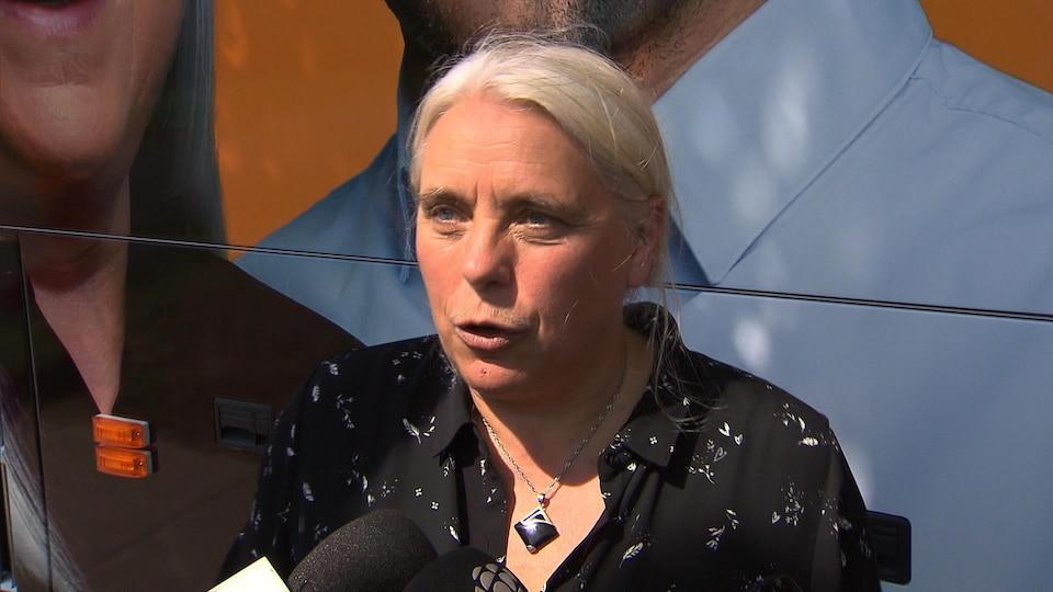 Manon Massé, interrogée par un journaliste devant l'autobus de campagne du parti.