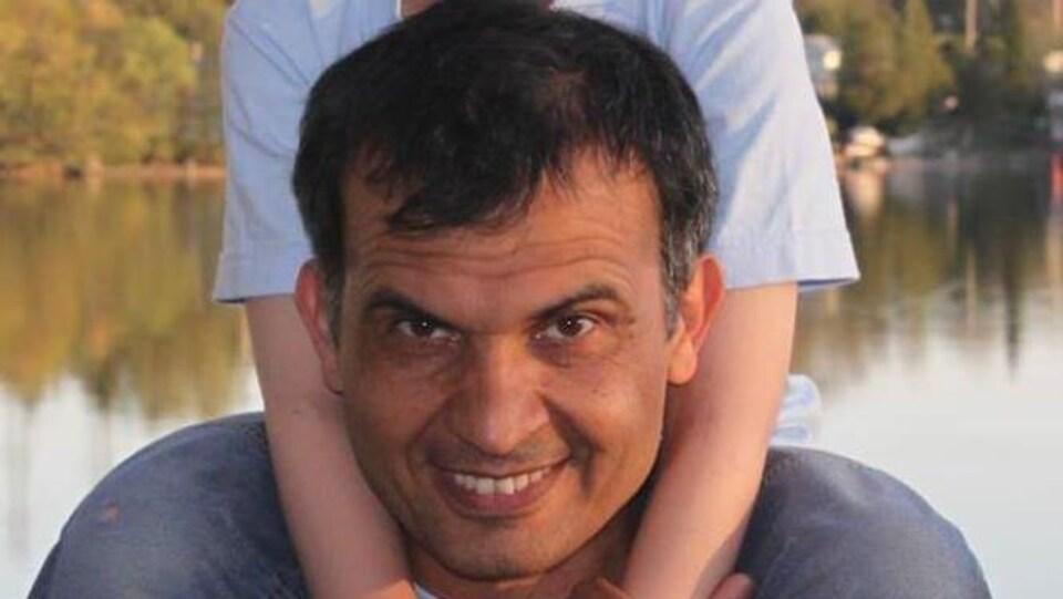 Mansour Pourjam souriant, tenant un enfant sur ses épaules.