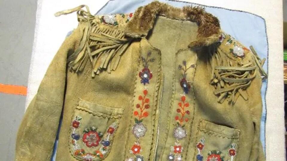 Un manteau avec le col en fourrure et des fleurs faites de petites billes de toutes sortes de couleur.