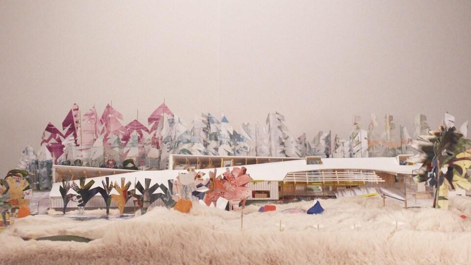 Maquette d'un bâtiment entouré d'arbres en papier.