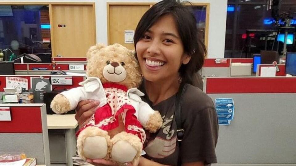 Une femme tient un ours en peluche et sourit.