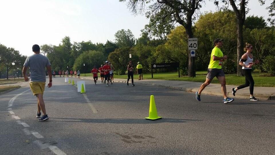 Des coureurs sur une route en bordure d'un parc.