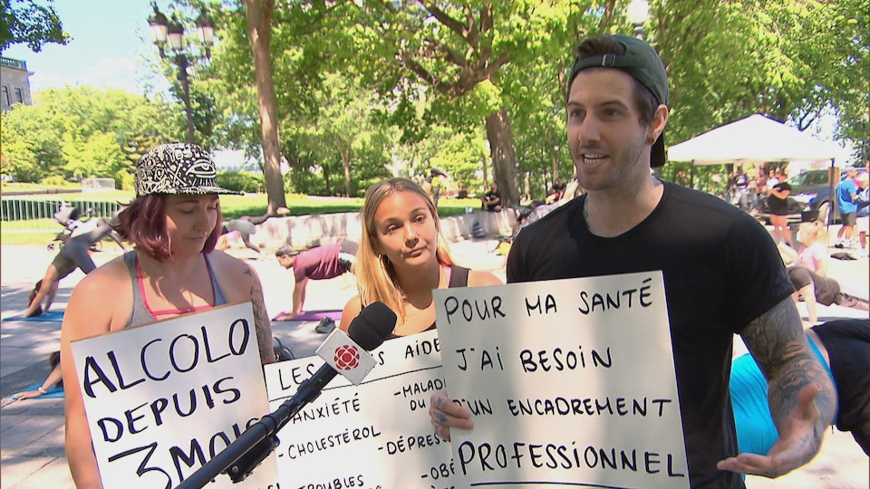 Trois personnes brandissent des pancartes pour réclamer l'ouverture des sutdios d'entraînement.