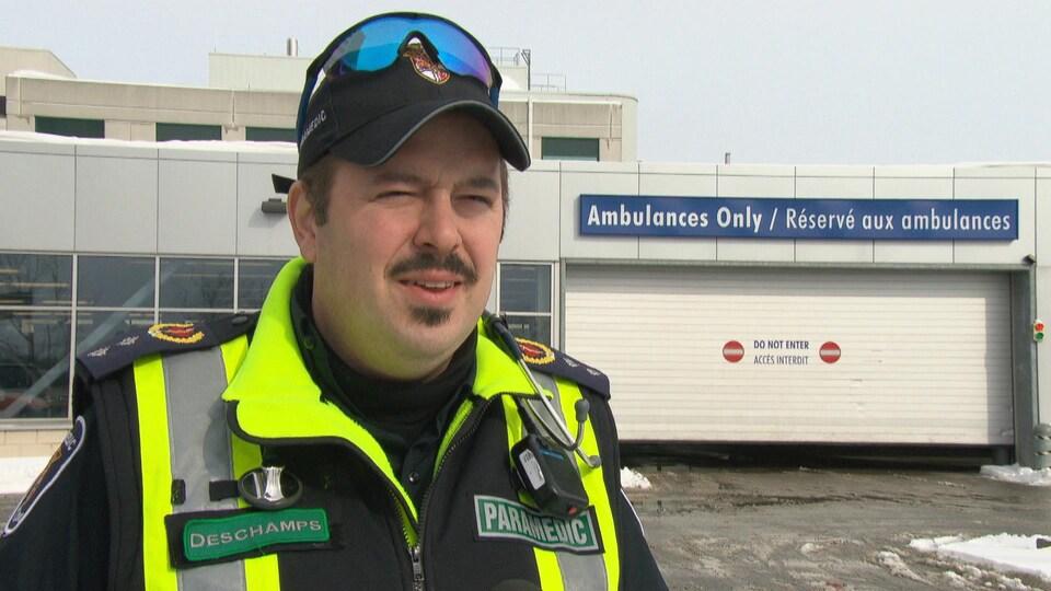Marc-Antoine Deschamps  porte son uniforme de paramédic et répond aux question d'un journaliste devant une porte de garage réservé aux ambulances.