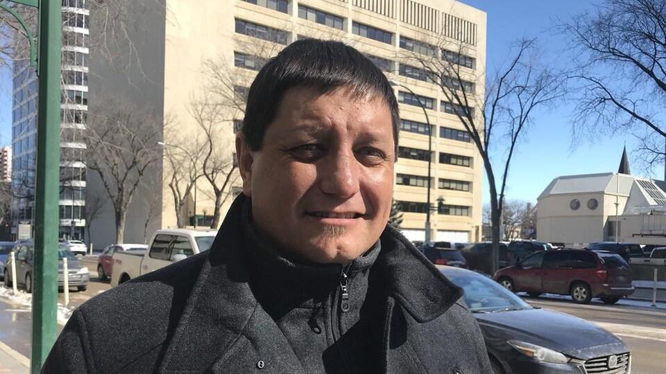 Mark Arcand sourit dans la rue, en entrevue.