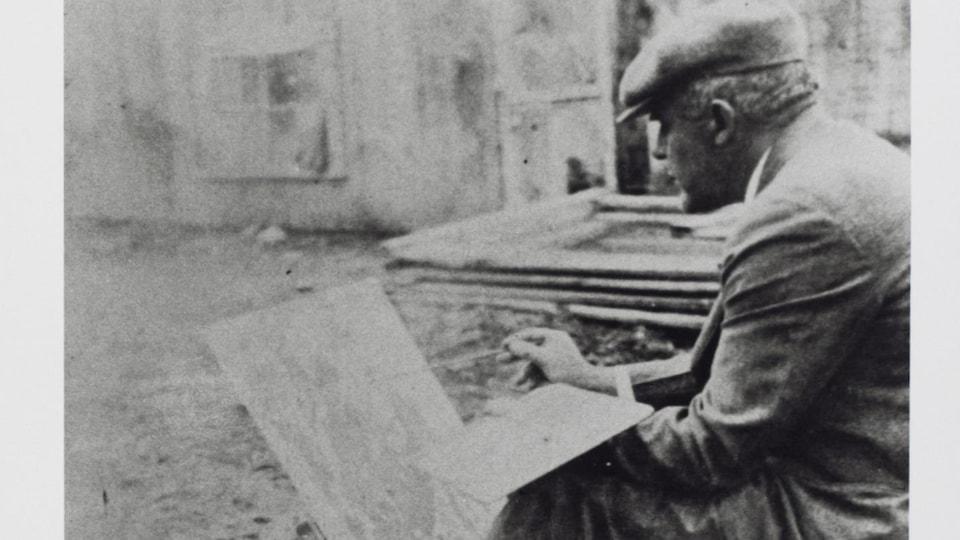 L'homme est assis par terre et peint une toile.