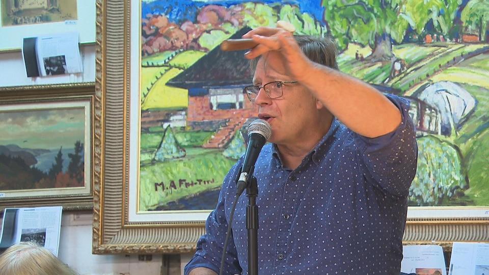 Un homme est devant un tableau de l'artiste peintre Marc-Aurèle Fortin