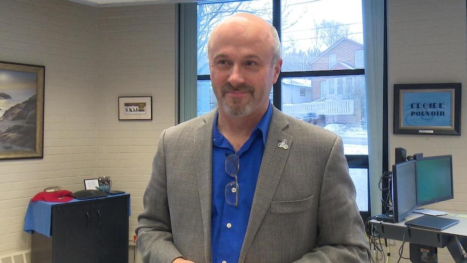 Un homme sourit debout dans son bureau.