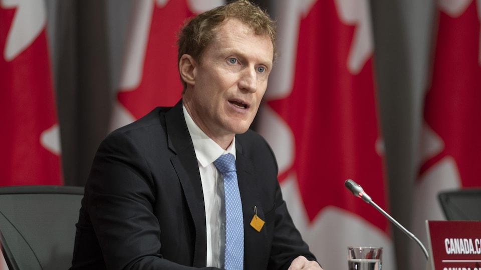 Marc Miller en conférence de presse devant plusieurs drapeaux du Canada.