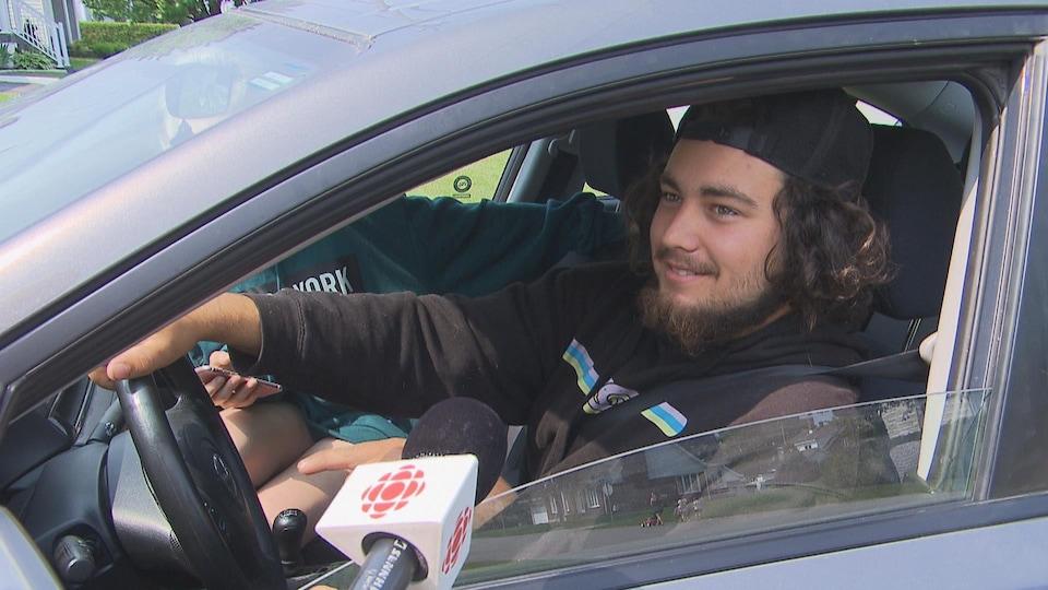 Jeune homme dans sa voiture avec un micro de Radio-Canada.