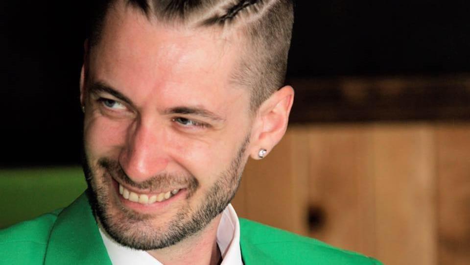 Un jeune homme en veston vert sourit en regardant vers la gauche.