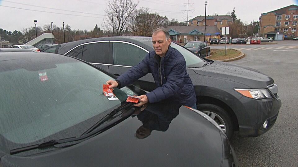 Un homme dépose un tract sur le pare-brise d'une voiture.