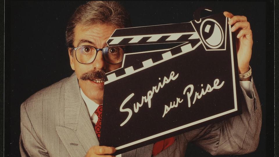Marcel Béliveau tient un clap de cinéma sur lequel il est écrit « Surprise sur prise ».