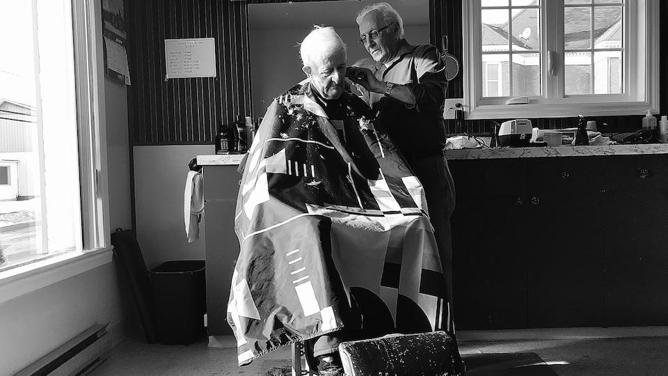 Un barbier de 76 ans coiffe un homme âgé.
