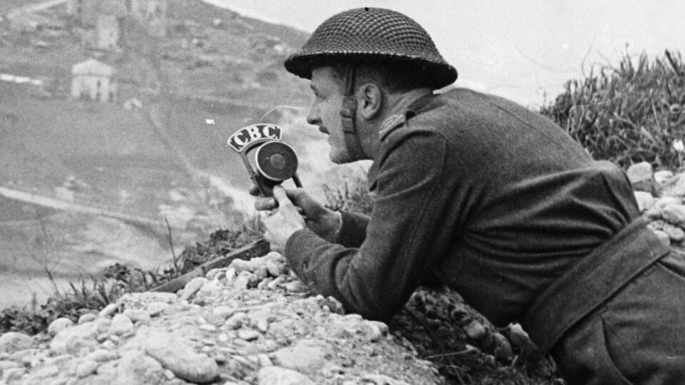 Juché sur une butte sur le front italien, le correspondant de guerre Marcel Ouimet, portant un casque militaire, enregistre un reportage un micro à la main.
