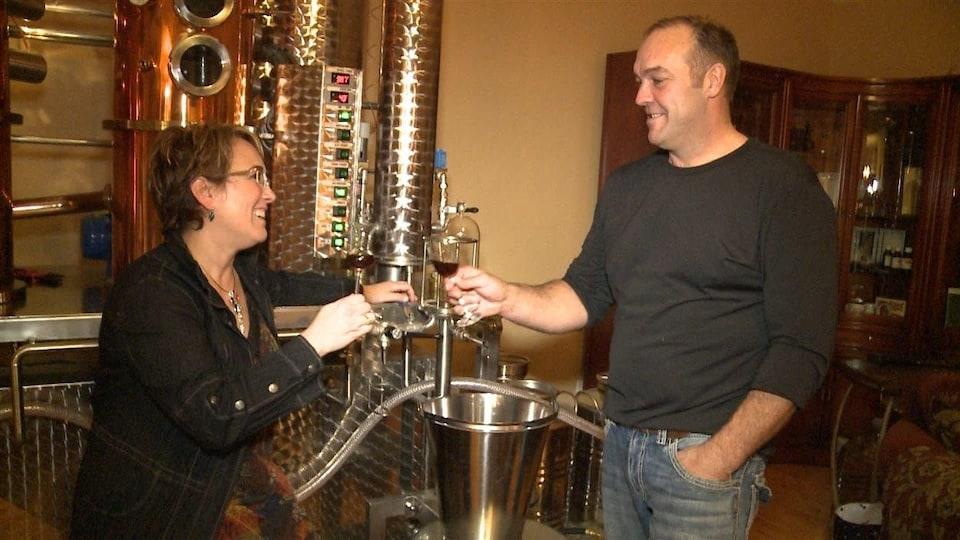 Un couple souriant qui tient des verres contenant un alcool sont debout devant un alambic de fer.
