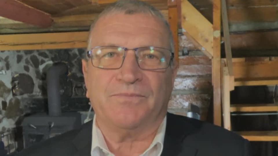 Un homme pendant une entrevue par visioconférence regarde droit devant l'objectif.
