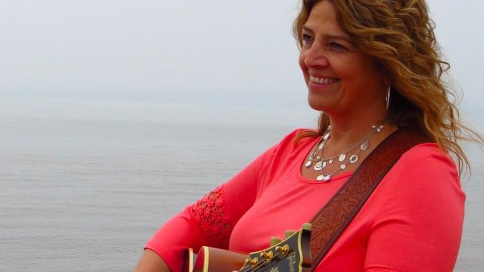 L'auteure-compositrice-interprète Marcella Richard joue la guitare à la plage.