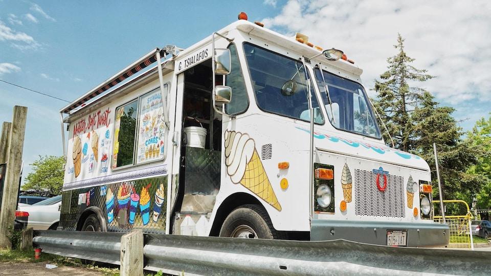 Un camion de crème glacée est stationné au bord d'une route.