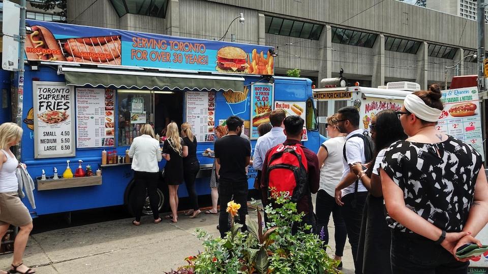 Une file de passants font la queue pour acheter de la nourriture à un marchand ambulant.
