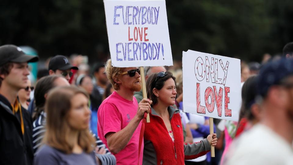 Des marcheurs portent des pancartes avec les messages «Tout le monde aime tout le monde», «Seulement l'amour».