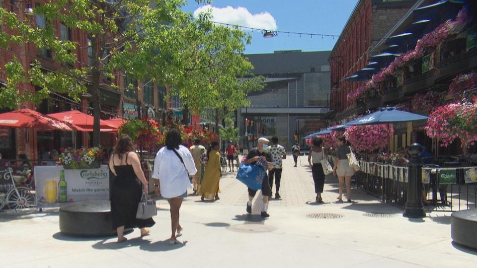 Des passants circulent sur une allée commerciale d'Ottawa, par une journée ensoleillée.