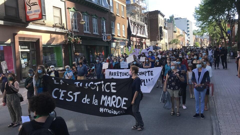 Des personnes marchent sur la rue Saint-Jean pour dénoncer la violence faite aux femmes.