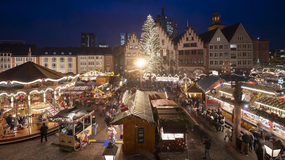 Plan panoramique du marché, avec ses stands, ses manèges et ses lumières.