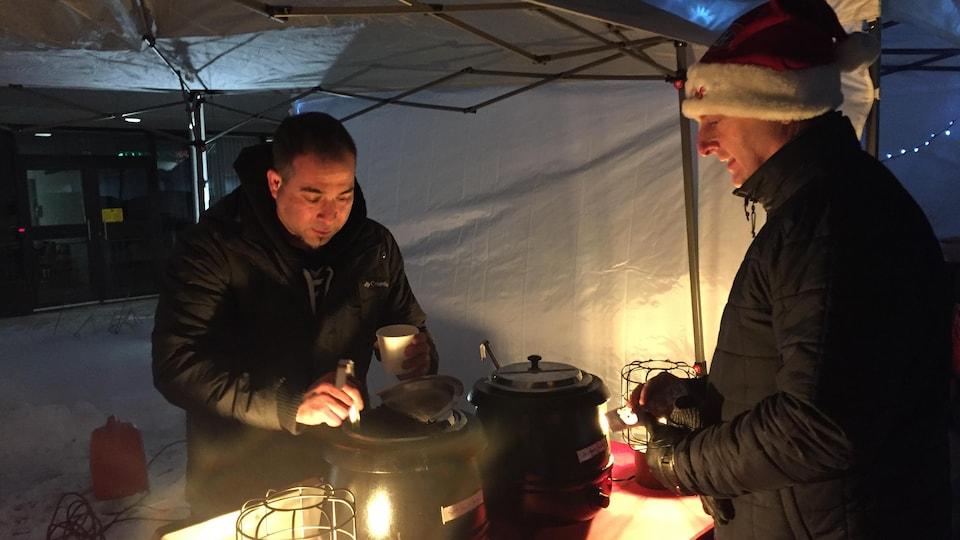 Un homme dans un kiosque sert une soupe à un client portant une tuque de Noël.