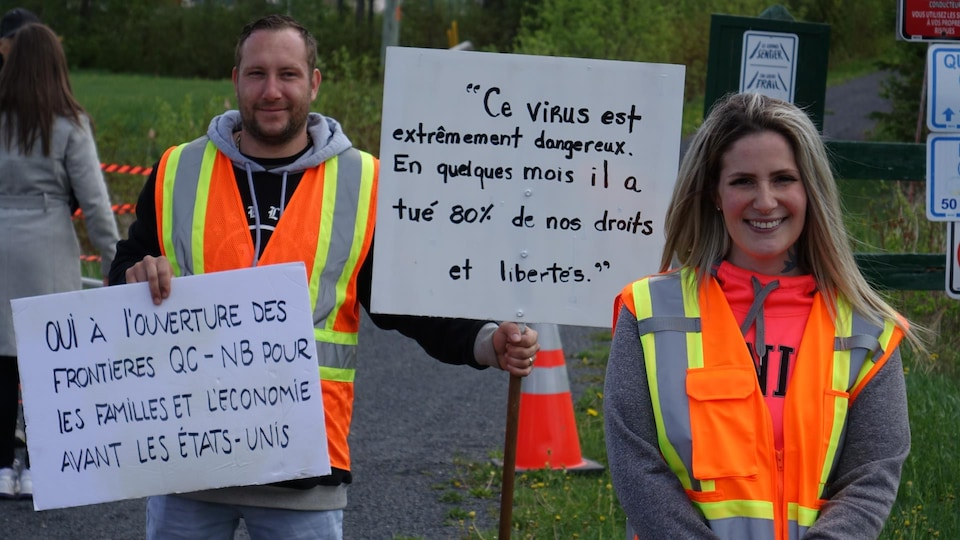 Des manifestants, dont Fanny Beaulieu Levesque, tiennent des pancartes.