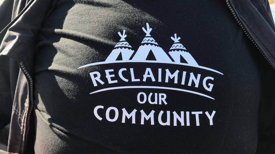 Un t-shirt portant le message «reclaiming our community».