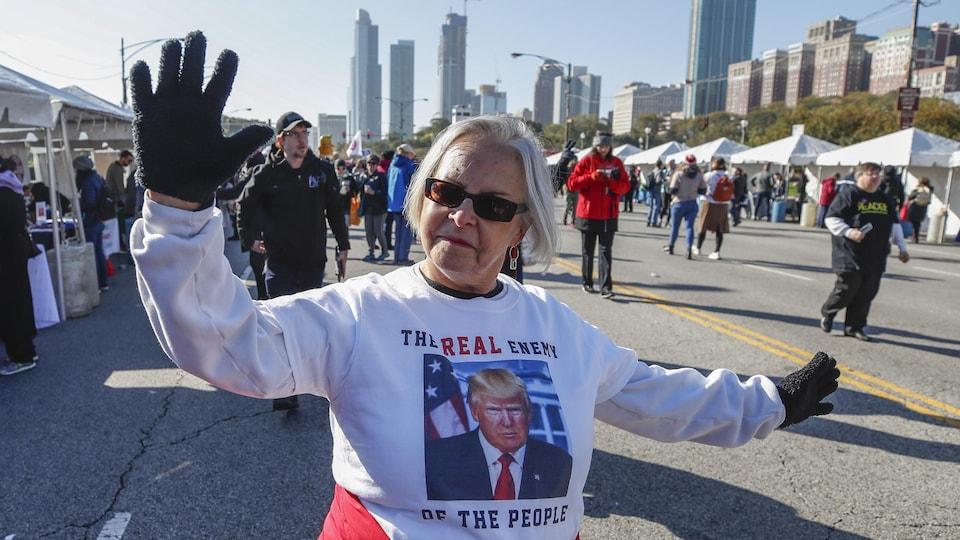 Une femme montre son opposition à Donald Trump en portant un chandail sur lequel est inscrit «Le vrai ennemi du peuple». En arrière d'elle, d'autres marcheurs commencent à se rassemble. En arrière-plan, des bâtiments du centre-ville de Chicago.