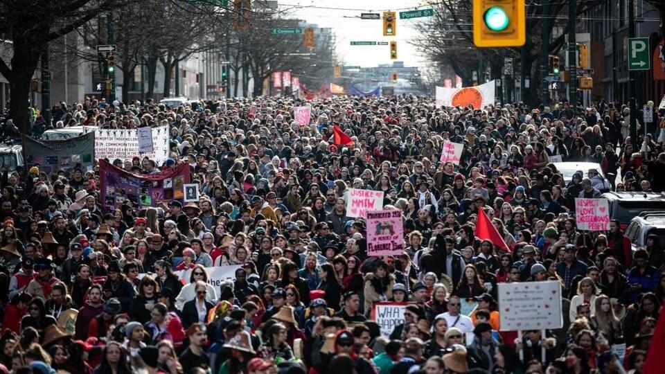 Des centaines de personnes marchent dans les rues de Vancouver.